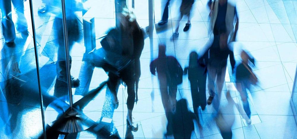 People walking through revolving door in office building